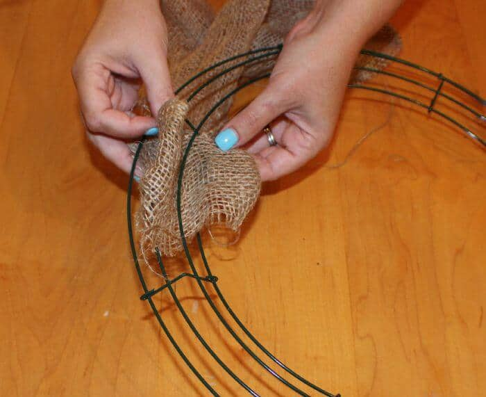 burlap wreath pull loops of butlap up between the three slots on the wire frame