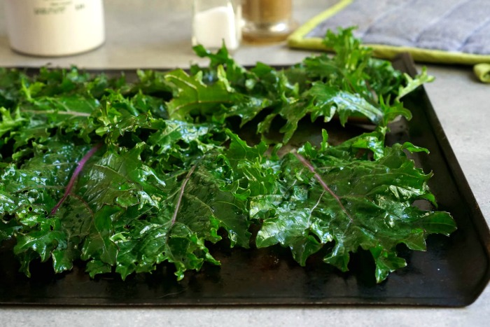 Roasted kale chips are baked on a tray in a single layer.
