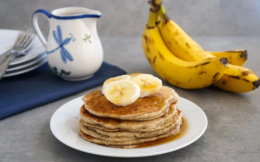 Vegan banana oat pancakes covered with fresh banana slices and pure maple syrup