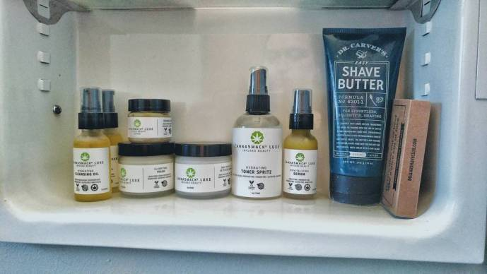 a line of skin care products by Cannasmack. From left to right: 2 bottles of hydrating cleansing oil, 1 jar of orange lip scrub placed atop a jar of clarifying polish scrub, a jar of daily moisture retention cream, a bottle of hydrating toner spritz, and a bottle of revitalizing serum. Unrelated, there is a bottle of Dr. Carver's Shaving Cream and 5-pack of razor replacements from Dollar Shave Club.