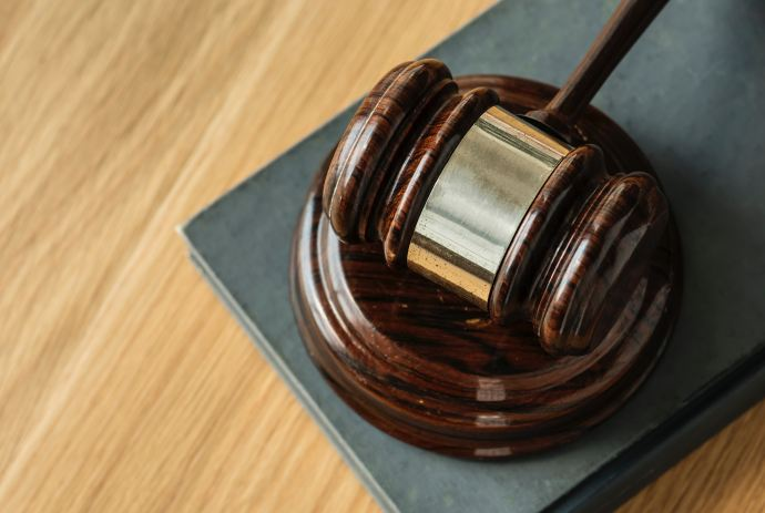 picture of brown, wooden judges gavel sitting on a wooden surface