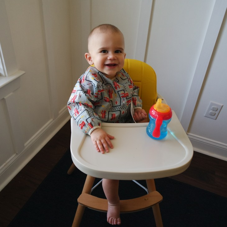 Baby in high chair with Munchkin sippy cup