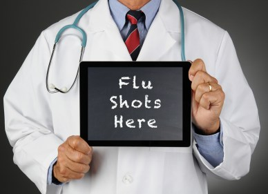 Closeup of a doctor holding a tablet computer with a chalkboard screen with the words Flu Shots Here.