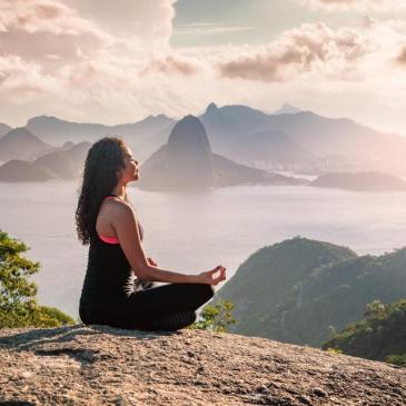 Woman meditating on mountain range
