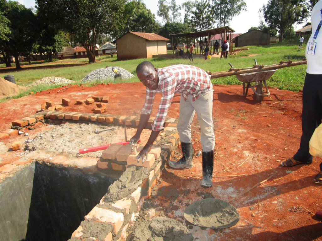 Paul Ivan Odongo utilizing his the vocational skills he gained in the Bricklaying and Concrete Practice department at PVTI