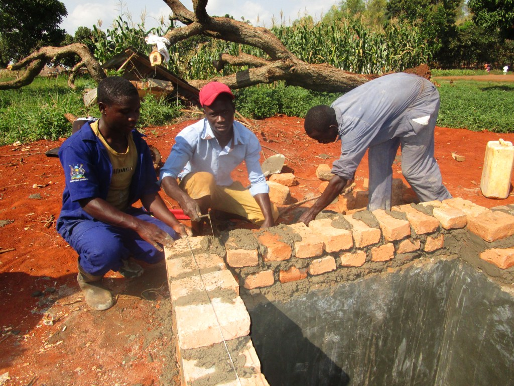 Paride Anur and Samuel Odongo employing the bricklaying skills they gained at PVTI
