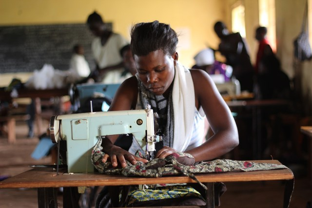 a woman sews a dress for a customer