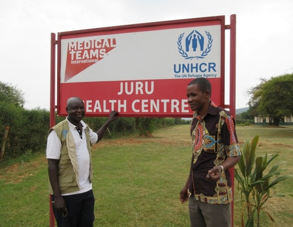 doctors pose next to hospital sign
