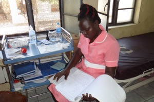 JCONAM third-year midwifery student reviewing files of women in the Maternity ward before administering medication