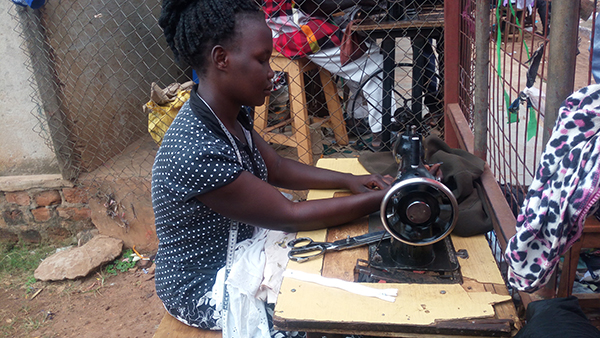 Vivian Adokorach works at a sewing table with a white garment in her lap