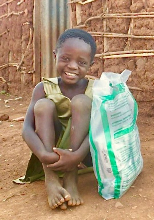 Sarah's oldest daughter, Hillary, poses with the bag of nutrition supplements that her family received from Lwala's nutritionist.