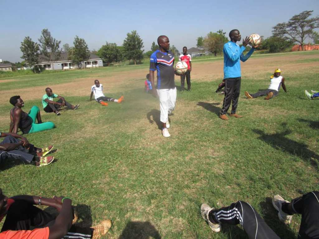 Mr. Haruna, a FUFA official, demonstrating practical skills to the coaches, who listen attentively