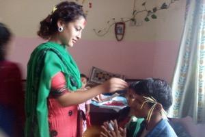 Nurse Pushpa applying tika to children