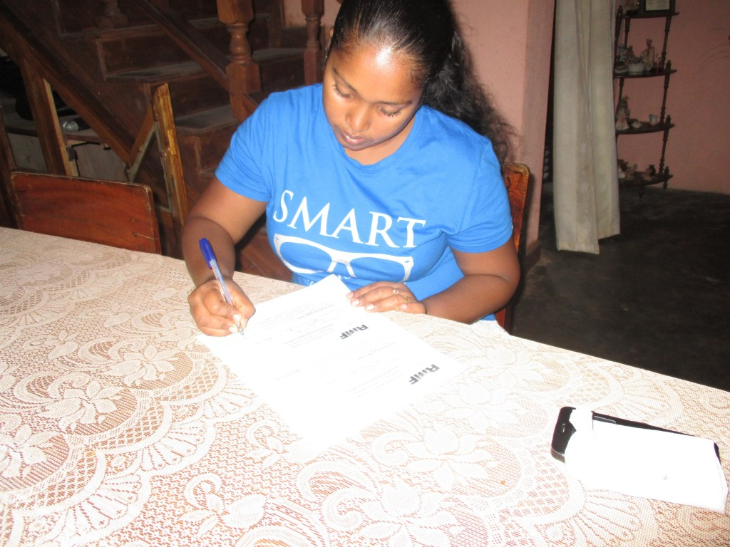 Tharindu's wife signs the paperwork