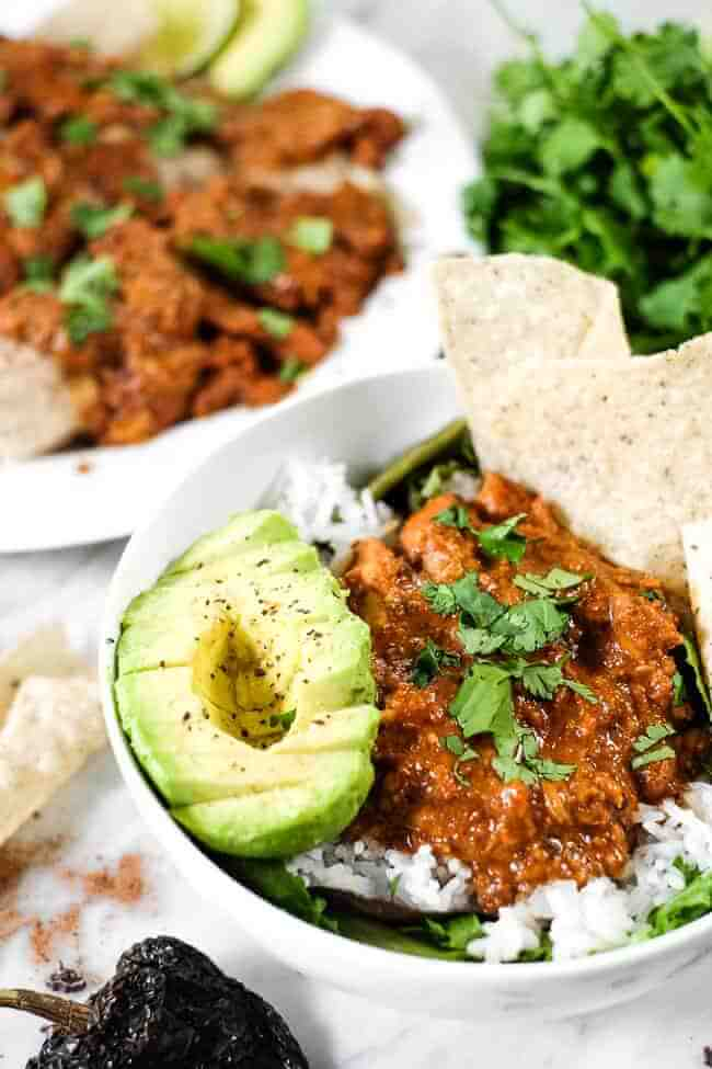 Chicken mole recipe in a bowl with greens, rice, avocado, grain free tortilla chips and chopped cilantro. Enchiladas in the background.