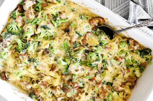 Horizontal image of spaghetti squash casserole in a large dish with serving spoon.