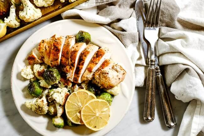 Easy lemon chicken served on a plate with roasted brussels and cauliflower and lemon slices for garnish, a grey and white striped napkin and silverware.