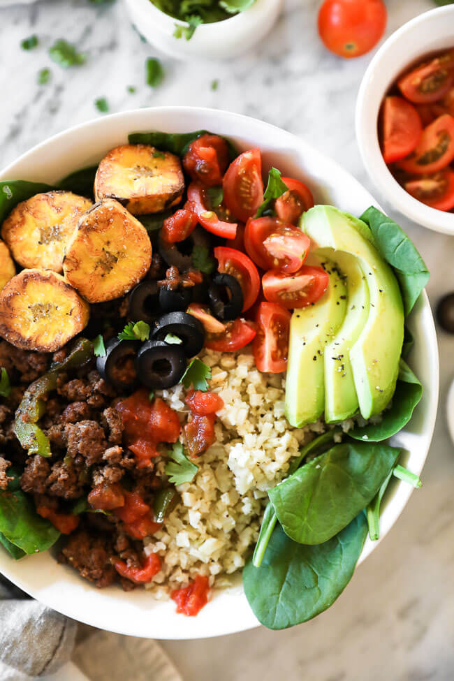 Close up image of ground beef taco bowl served with cauliflower rice, tomatoes, olives, salsa, fried plantains, avocado and chopped cilantro.