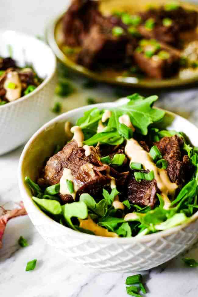 Instant pot short ribs served in a bowl with greens and topped with mayo sauce and chopped green onion.