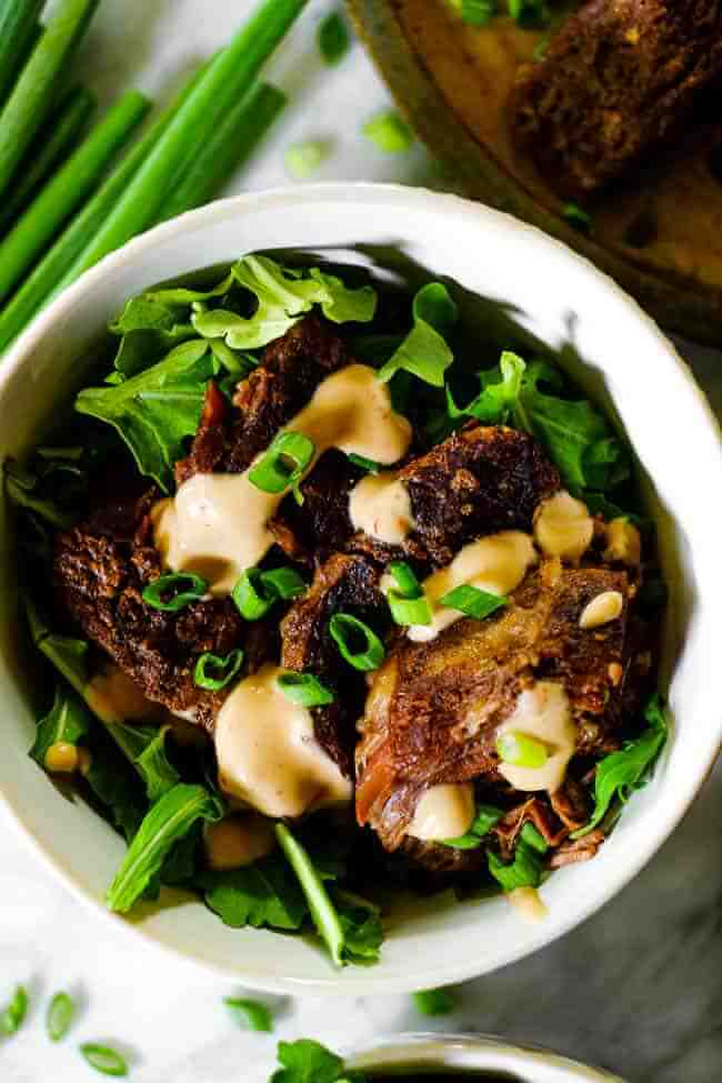 Close up overhead shot of instant pot short ribs in a bowl with greens, mayo sauce and chopped green onion.