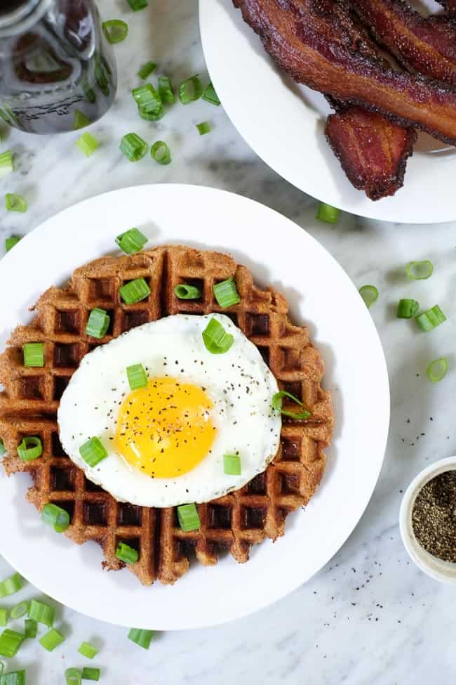 Savory Paleo waffles topped with a fried egg and green onion.