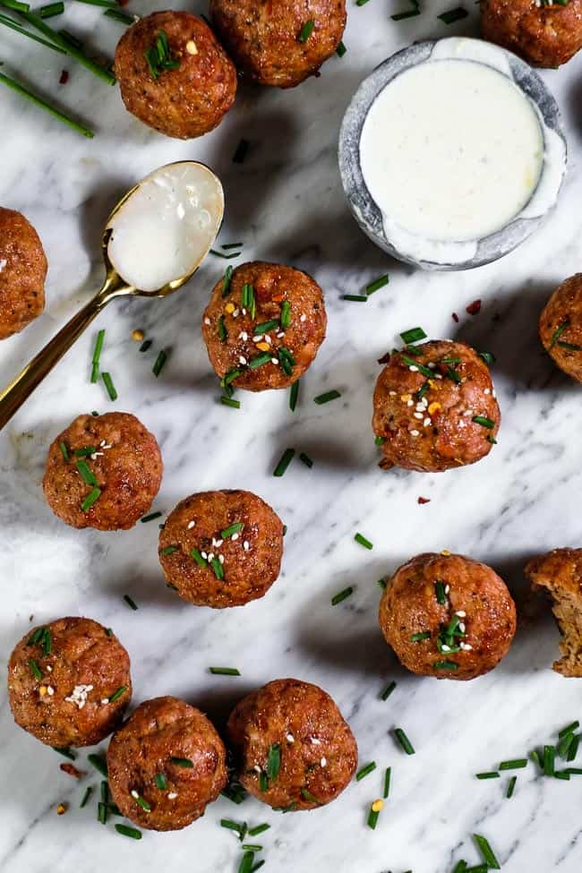 Pork meatballs topped with chopped chives, red pepper chili flakes and sesame seeds spread out on marble with a side of ranch dressing.