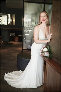 Gown from The Clothes Mine; Earrings by Sorrelli Jewelry; Bouquet by Hillside Blooms Floristry; Hair and makeup by All Dolled Up Hair and Makeup Artistry; Photo by 2 Girls 20 Cameras, on location at Kimpton Sawyer Hotel