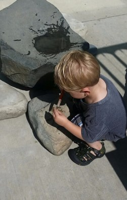 young boy at play painting on rocks with water