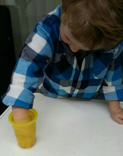 Preschooler discovers simple science principle of measuring volume through water displacement by putting his hand in a cup of water