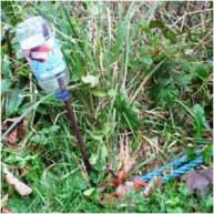 The bottle on the left has been used as a safety measure to stop people hurting themselves on a stake.
