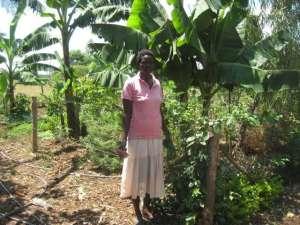 Yunis standing by the medicinal garden she teaches from