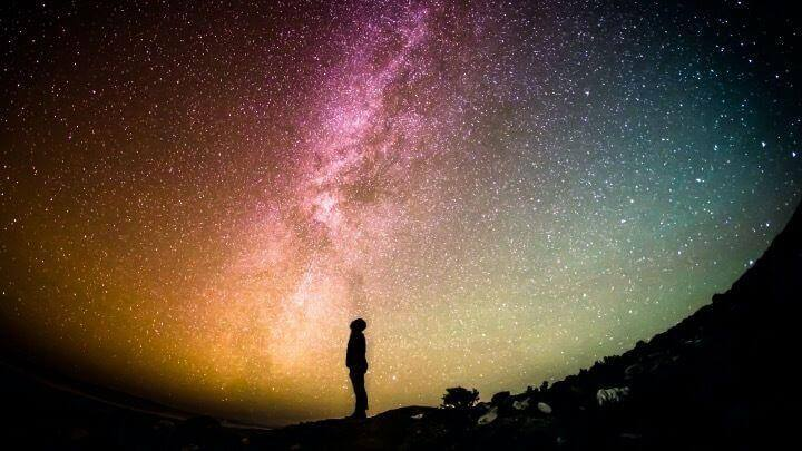 Person standing at night with background of milky way