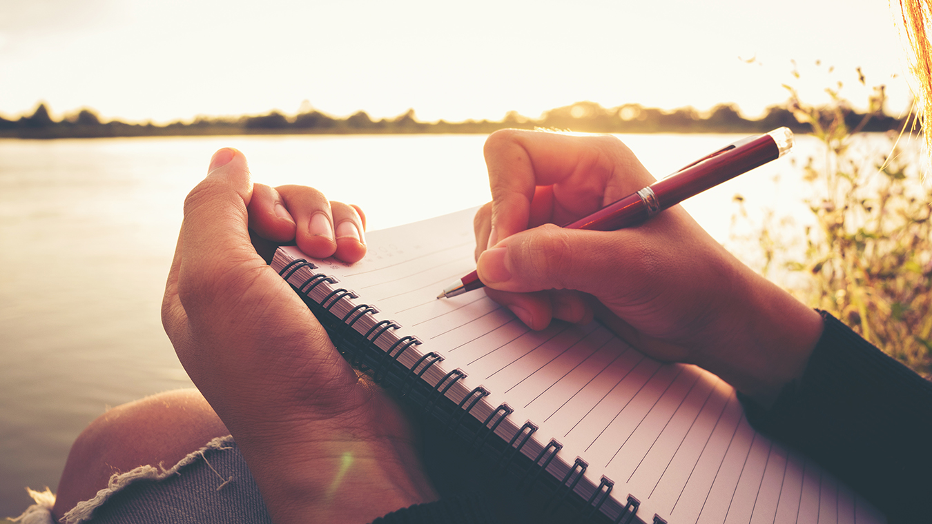 Close up hand of young woman with pen writing on notebook at riv
