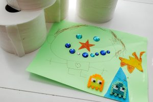 Photo of a child's mixed-media collage with toilet paper rolls in the background.