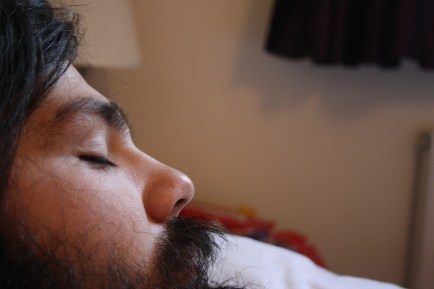 A side profile of a male. Predominately his eyes, nose, mouth and portion of the beard is in shot. The backdrop is unfocused, but you can vaguely make out a lampshade and curtains.