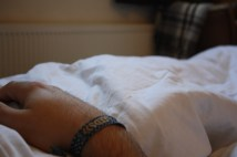 A photograph os a males hand./wrist upon white bedsheets. The backdro of a radiator and blanket is unfocused and enhances the technique of depth of field