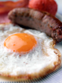 Tim Hill describes this image as: 'A food photograph of a fried egg with a golden yolk, some tomatoes and a sausage with a rasher of bacon, a cooked breakfast.'
