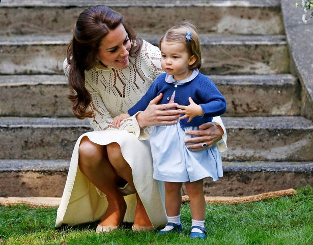 Britains-Catherine-Duchess-of-Cambridge-speaks-to-Princess-Charlotte-as-they-arrive-at-a-children.jpg