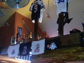 A combination of Dallas Cowboys paraphenalia and trophys decorate the indoor beams.