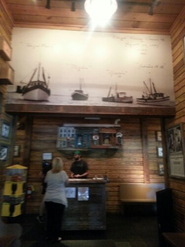 The hostess stand sits under a large image of sail boats, making a huge statement and first impression.