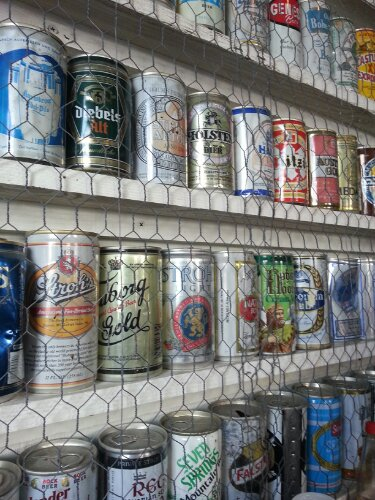Beer cans from around the world decorate the walls secured behind chicken wire.