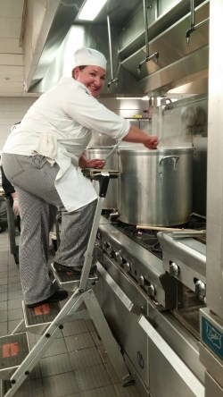 Climbing the step ladder to stir 18 gallons of tomato bisque.