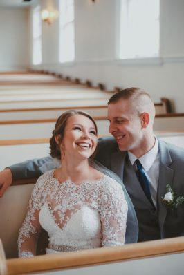 bride and groom seated on white pews