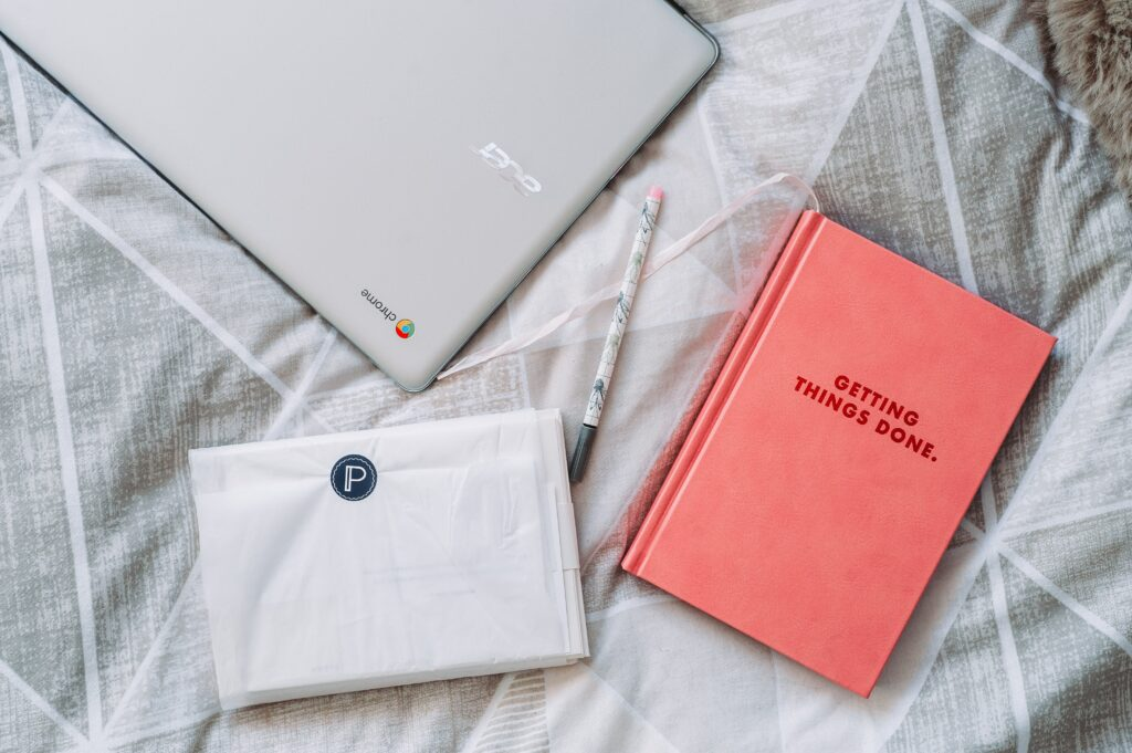 A pink notebook with 'getting things done' written on it, with a white chromebook laptop and a white pen on a white bedsheet