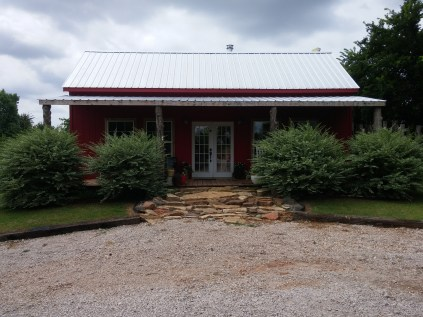 The front of the house. There are rocking chairs behind the shrubs.