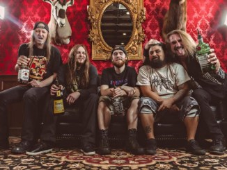 Warbeast band members posing in a red room