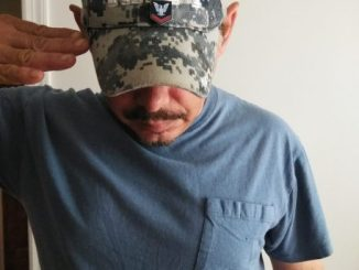 Rebel Radio's Kevin Lane saluting while wearing his Navy cap on Veterans Day