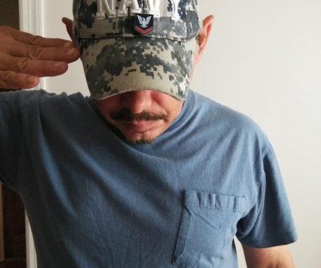 Rebel Radio's Kevin Lane saluting while wearing his Navy cap on Veterans Day