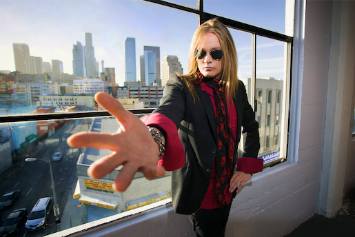 Sebastian Bach, standing in front of a window, facing the skyline of a city