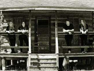 Temptress band members standing on porch of a wooden house, black and white